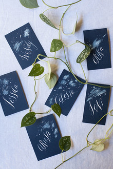 Blue escort cards with white calligraphy