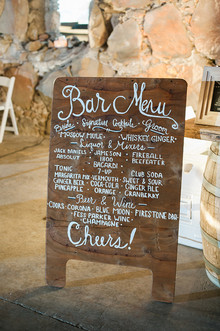 Wooden bar menu with white calligraphy