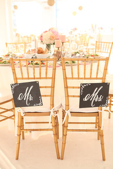 Mr. and Mrs. signage on gold chairs