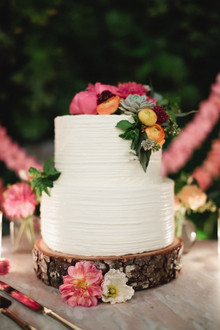 White cake with wood base and colorful flowers