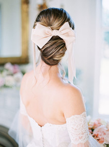 romantic bridal updo with pink bow