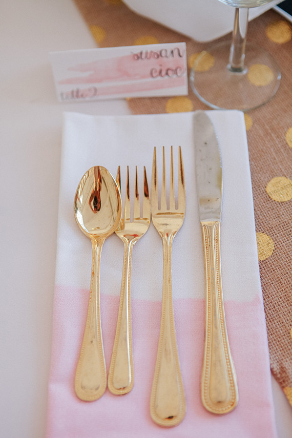 Gold flatware with pink and white napkin