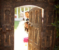 Bride and Groom Peeking Behind Doorway Portait