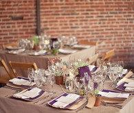 Square reception tables with purple napkin accents