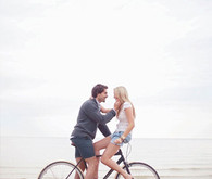 Casual couple on a bike at the beach