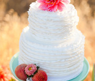 White wedding cake with flower topper