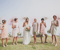 Pink and cream bohemian bridesmaids with pink umbrellas
