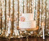 Gold stand with white cake and candles