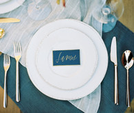 Blue white and gold place setting with escort card