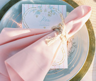 Nautical wedding place setting with pink napkin