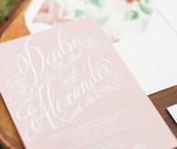 Light pink invitation with white writing