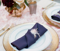 Gold plate with purple napkin and feather accent