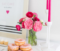 Bright pink floral centerpiece with pink donuts