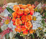 Orange rose and blue floral centerpiece