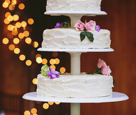 Four tiered white wedding cake with cupcakes