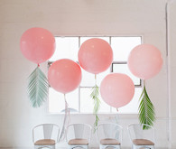 Pink balloons with tropical foliage