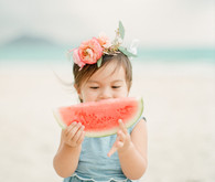 little girls on the beach with flower crowns and watermelon