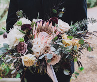 Black groom's suit with protea bouquet