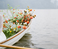 End of summer retro engagement shoot in a rowboat full of flowers
