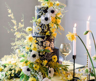 black wedding cake with anenomes and yellow flowers