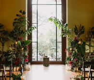 dramatic hollywood wedding ceremony with tropical plants