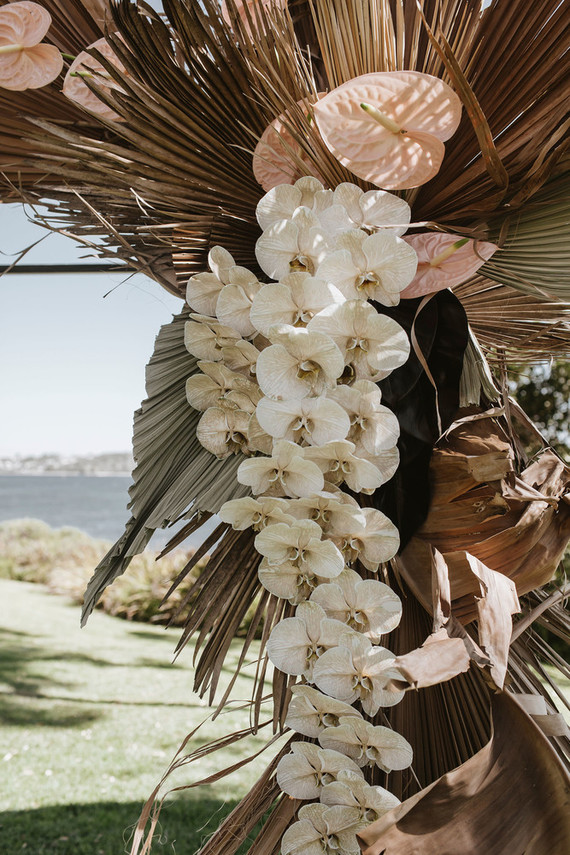 Palm leaf and orchid ceremony arch